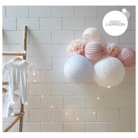 Chambre bebe rose pale et blanche : décoration murale avec des pompons et lampions.