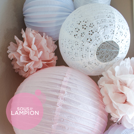 Pink nursery decor with paper lanterns and pompoms