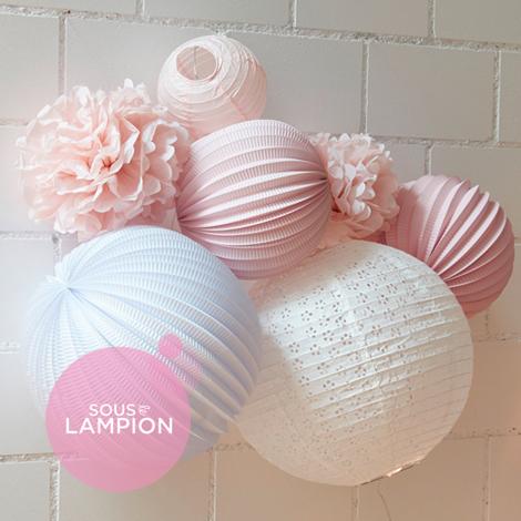 Décoration de chambre de bébé rose et blanche avec des boules papier et des pompons